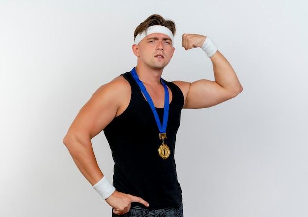 Pewny siebie młody przystojny sportowy mężczyzna noszący opaskę i opaski na nadgarstek oraz medal na szyi, kładący rękę na talii i gestykulujący silny na białym tle