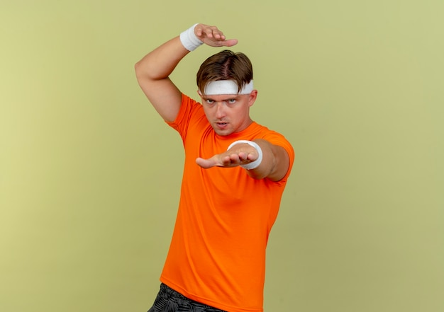 Pewny siebie młody przystojny sportowy mężczyzna noszący opaskę i opaski na nadgarstek wyciągający rękę i trzymający inny nad głową odizolowany na oliwkowej zieleni z miejscem na kopię