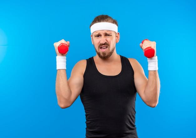 Pewny siebie młody przystojny sportowy mężczyzna noszący opaskę i opaski na nadgarstki trzymający hantle izolowane na niebieskiej ścianie