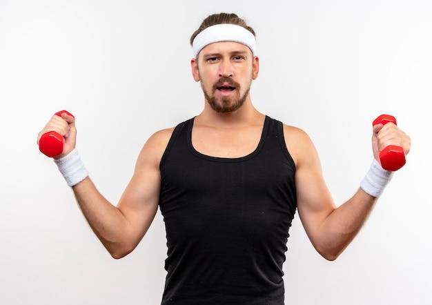 Pewny siebie młody przystojny sportowy mężczyzna noszący opaskę i opaski na nadgarstki trzymający hantle patrzący na białym tle na białej ścianie