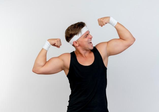 Pewny siebie młody przystojny sportowy mężczyzna noszący opaskę i opaski na rękę, gestykulując silny i patrząc na jego mięśnie na białym tle