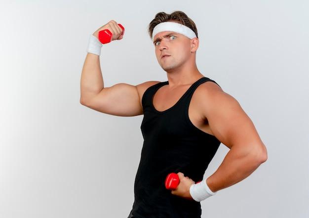 Pewny siebie młody przystojny sportowy mężczyzna noszący opaskę i opaski na rękę stojący w widoku profilu, trzymając i podnosząc hantle, gestykulując silny na białym tle