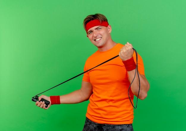 Pewny siebie młody przystojny sportowy mężczyzna ubrany w opaskę i opaski na rękę ciągnąc skakankę na białym tle na zielono