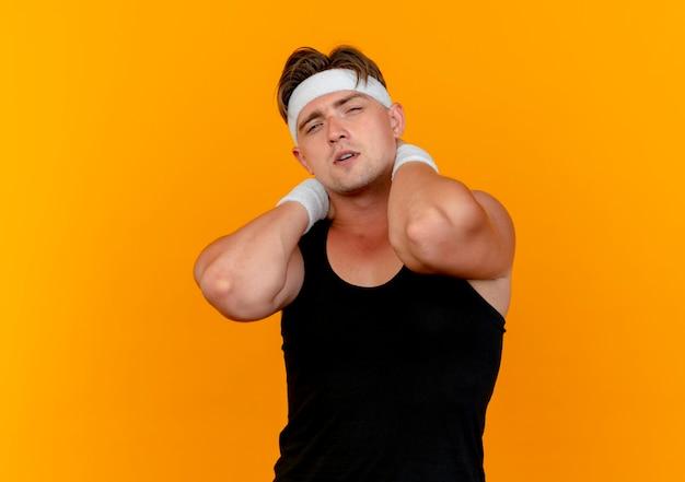 Pewny siebie młody przystojny sportowy mężczyzna ubrany w opaskę i opaski na rękę kładąc ręce za szyję na pomarańczowym tle z miejsca na kopię