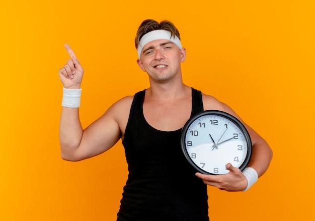 Pewny siebie młody przystojny sportowy mężczyzna ubrany w opaskę i opaski na rękę trzyma zegar i wskazuje w górę na białym tle na pomarańczowo
