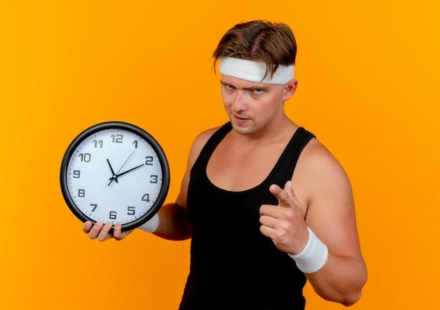 Pewny siebie młody przystojny sportowy mężczyzna ubrany w opaskę i opaski na rękę, trzymając zegar i wskazując na białym tle na pomarańczowo