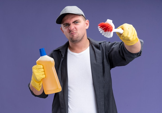 Pewny siebie młody przystojny sprzątacz sobie t-shirt z czapką i rękawiczkami, trzymając środek czyszczący i trzymając pędzel na białym tle na fioletowej ścianie