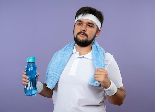 Pewny siebie młody sportowiec sobie opaskę na głowę i opaskę z ręcznikiem na ramieniu, trzymając butelkę wody