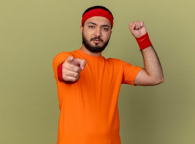 Pewny siebie młody sportowiec w opasce i opasce pokazuje silny gest