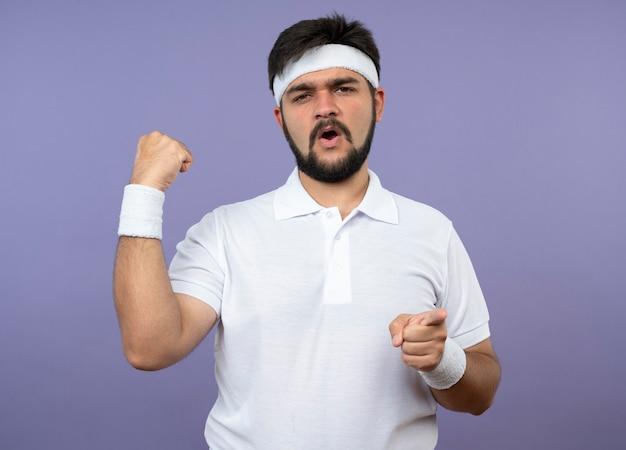 Pewny siebie młody sportowiec w opasce i opasce robi silny gest i wskazuje