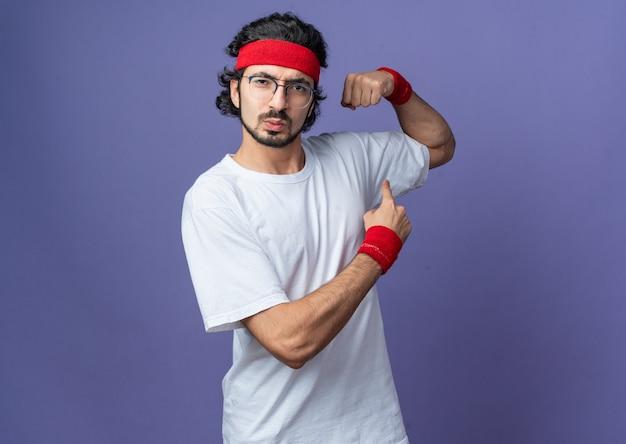 Pewny siebie młody sportowy mężczyzna noszący opaskę z opaską na nadgarstek robiący silny gest