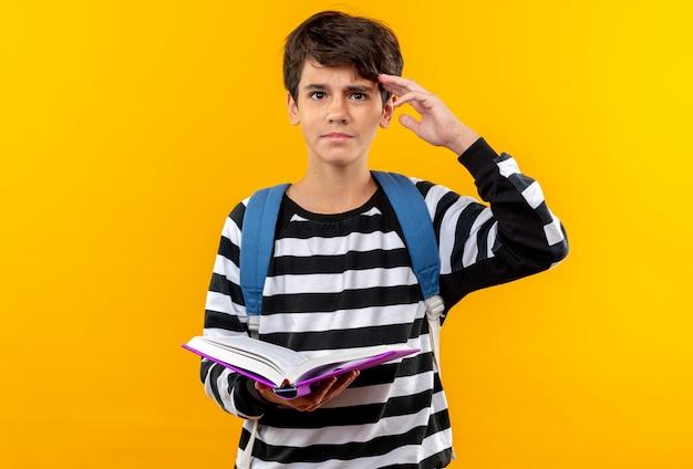 Pewny siebie młody szkolny chłopiec noszący plecak trzymający książkę pokazujący gest salutu odizolowany na pomarańczowej ścianie