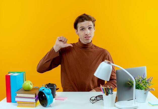 Pewny siebie młody uczeń chłopiec siedzi przy biurku z narzędzi szkolnych wskazuje na siebie