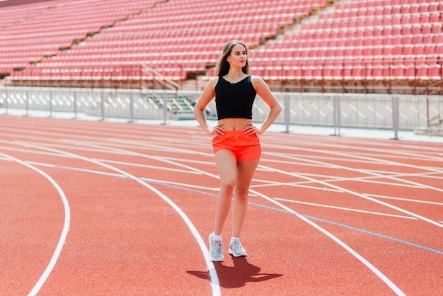 Pewny siebie nastolatek sportowca w sportowej pozycji na torze na stadionie