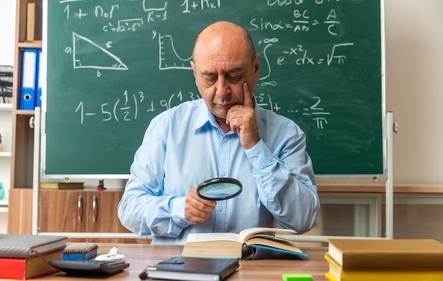 Pewny siebie nauczyciel w średnim wieku siedzi przy stole z przyborami szkolnymi, czytając książkę z lupą kładącą dłoń w policzek w klasie