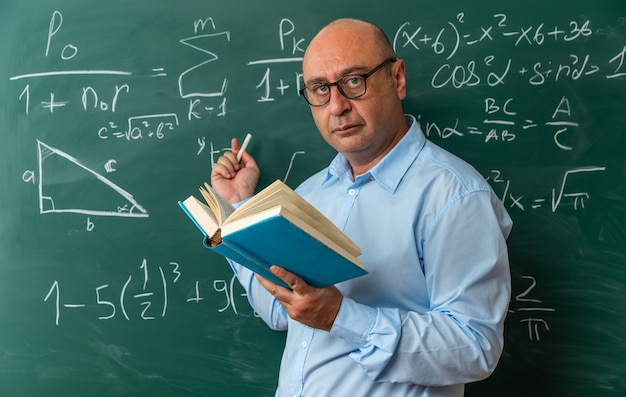 Pewny siebie nauczyciel w średnim wieku w okularach stojący przed tablicą trzymającą książkę