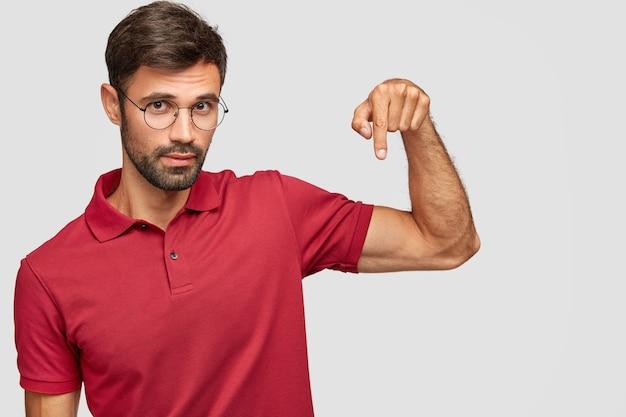 Pewny siebie nieogolony model męski w okularach i czerwonej koszulce, wskazuje w dół