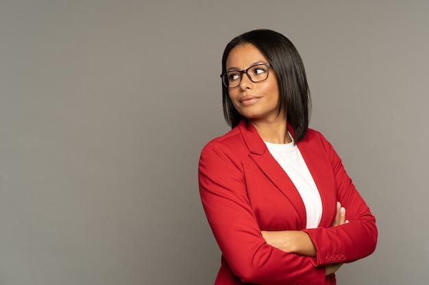 Pewny siebie, odnoszący sukcesy bizneswoman stoi z założonymi rękoma, patrząc z boku na pustą przestrzeń nad szarą ścianą