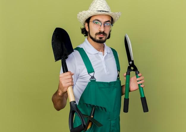 Pewny siebie ogrodnik mężczyzna w okularach optycznych na sobie kapelusz ogrodniczy trzyma łopatę i maszynki do strzyżenia