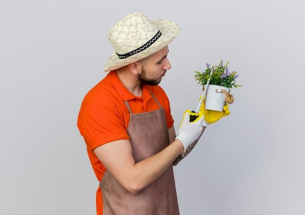 Pewny siebie ogrodnik w kapeluszu ogrodniczym mierzy doniczkę z centymetrem