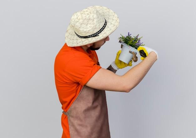 Pewny siebie ogrodnik w kapeluszu ogrodniczym wygląda i mierzy doniczkę z centymetrem