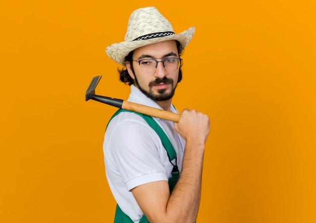 Pewny siebie ogrodnik w okularach optycznych na sobie kapelusz ogrodniczy trzyma grabie motyka na ramieniu