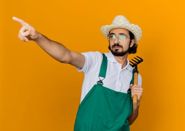 Pewny siebie ogrodnik w okularach optycznych w kapeluszu ogrodniczym trzyma grabie i wskazuje na bok