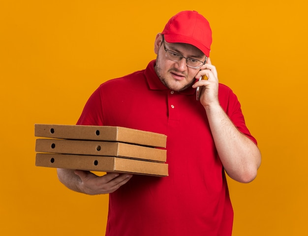 Pewny siebie, otyły, młody kurier w okularach optycznych, trzymając pudełka po pizzy i rozmawiając przez telefon na pomarańczowej ścianie z miejsca na kopię