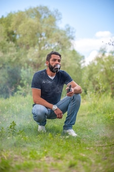 Pewny siebie palacz pali papierosa, wydycha dym.