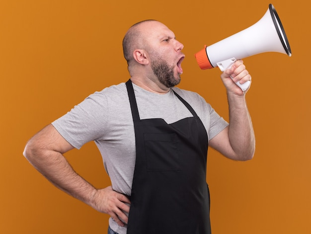 Pewny siebie patrząc na bok fryzjera męskiego w średnim wieku w mundurze mówi przez głośnik, kładąc rękę na biodrze na pomarańczowej ścianie