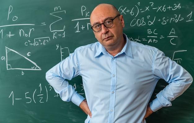 Pewny siebie, patrzący na kamerę nauczyciel w średnim wieku w okularach, stojący przed tablicą, kładąc ręce na biodrach