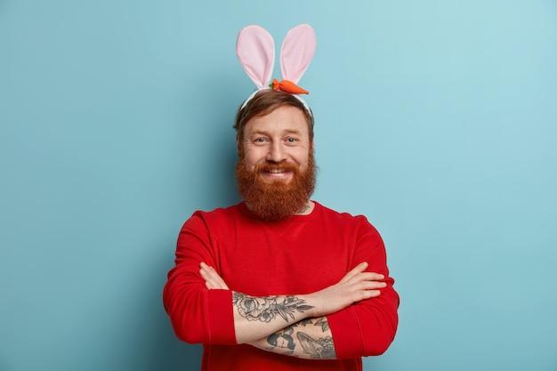 Pewny siebie, pewny siebie młody mężczyzna z gęstą rudą brodą nosi królicze uszy