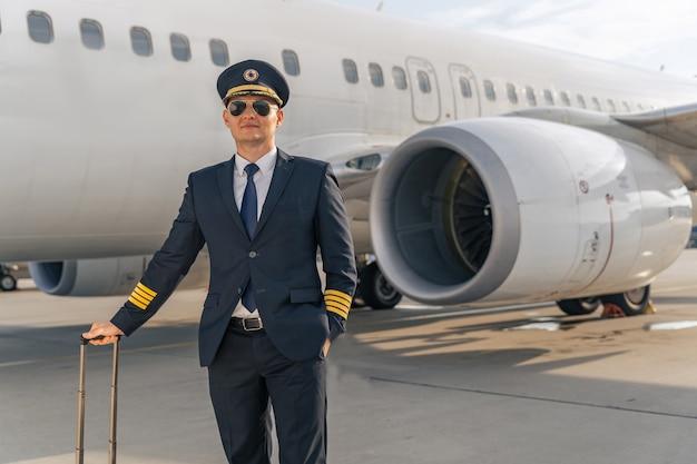 Pewny siebie pilot uśmiechający się przed wielkim samolotem