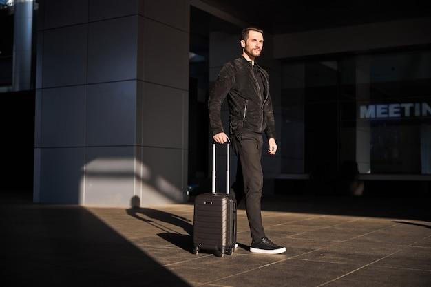 Pewny siebie podróżnik idący sam ze swoją walizką