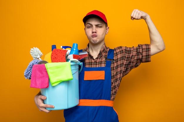 Pewny siebie, pokazując silny gest, młody facet sprzątający ubrany w mundur i czapkę, trzymający wiadro z narzędziami do czyszczenia