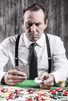 Pewny siebie pokerzysta. poważny starszy mężczyzna w koszuli i szelkach siedzi przy stole pokerowym i trzyma karty i żetony