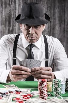 Pewny siebie pokerzysta. zbliżenie: poważny starszy mężczyzna w koszuli i szelkach siedzący przy stole pokerowym i trzymający karty z pieniędzmi i żetonami do gry leżącymi wokół niego