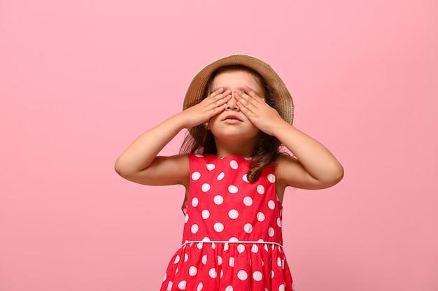 Pewny siebie portret przepięknej dziewczynki ubranej w letnią sukienkę w kropki i słomkowy kapelusz, zasłaniając oczy rękoma, pozowanie na różowym tle z miejscem na tekst na reklamę