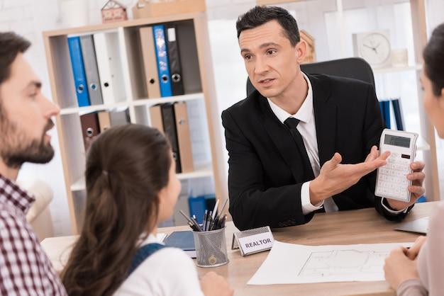 Pewny siebie pośrednik pomaga młodej rodzinie sprzedawać nieruchomości