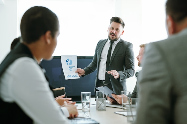 Pewny siebie pośrednik w eleganckim garniturze i krawacie pokazujący na spotkaniu papier ze schematem finansowym dla młodych międzykulturowych kolegów lub partnerów