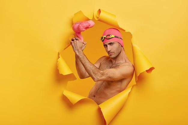 Pewny siebie poważny facet z włosiem trzyma nadmuchanego różowego flaminga, nosi czepek kąpielowy z goglami na czole