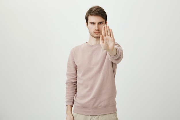 Pewny siebie, poważny mężczyzna wyciąga rękę, aby zatrzymać, zabronić lub zabronić działania