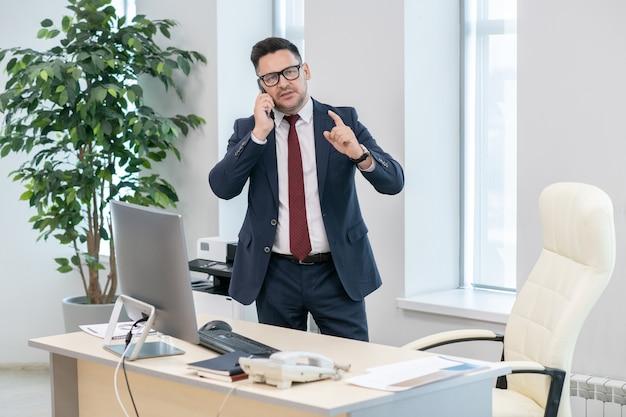 Pewny siebie pracodawca w eleganckim garniturze omawia przez telefon warunki umowy