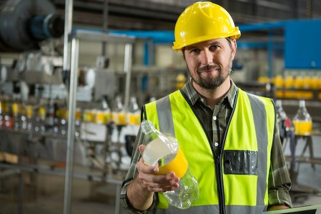 Pewny siebie pracownik płci męskiej sprawdzający butelki w fabryce soków