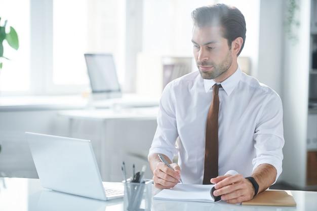 Pewny siebie pracownik robi notatki podczas oglądania wideo online przed laptopem w biurze