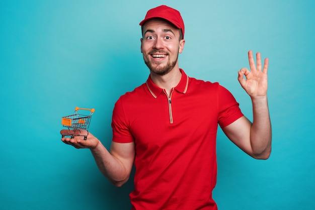 Pewny siebie pracownik z czerwonym mundurem gwarantuje zakupy online. cyjanowa ściana