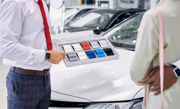 Pewny siebie profesjonalny konsultant kaukaski pokazuje klientom paletę kolorów samochodów