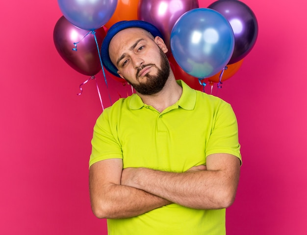 Pewny siebie, przechylająca się głowa młody człowiek ubrany w niebieski kapelusz imprezowy stojący przed balonami, skrzyżowanymi rękami odizolowanymi na różowej ścianie