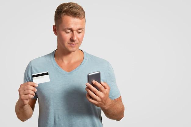Pewny siebie, przyjemnie wyglądający mężczyzna trzyma nowoczesną komórkową i plastikową kartę, sprawdza swoje konto bankowe