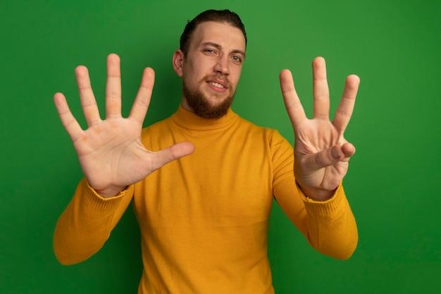 Pewny siebie przystojny blondyn gestykuluje osiem palcami odizolowanymi na zielonej ścianie